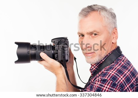 Side view of aged photographer holding a camera Zdjęcia stock ©