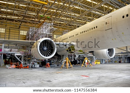 Side view of aircraft (airplane)engine during lift up from the floor by aircraft jack for maintenance at aircraft hangar.Aircraft on jack in hangar for maintenance service check by mechanic.