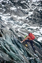 Side view of alpinist with backpack using rope while climbing alpine ridge. Male climber ascending mountain cliff, trying to reach mountaintop. Concept of mountaineering, alpinism and alpine climbing.