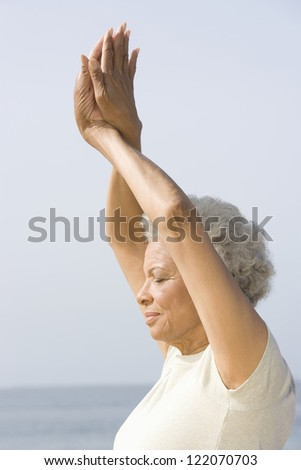 Side view of an African American senior woman practicing yoga against sky - stock photo