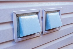 Side view of an Air Wall Cap. Vent cap outside building. Furnace duct outside of a residencial house