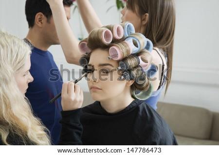 Side view of an artist applying eyeshadow to female model