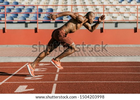 Side view of an athlete starting his sprint on an all-weather running track