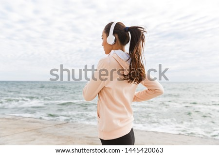 Side view of an attractive young asian fitness woman jogging at the beach, listening to music with headphones