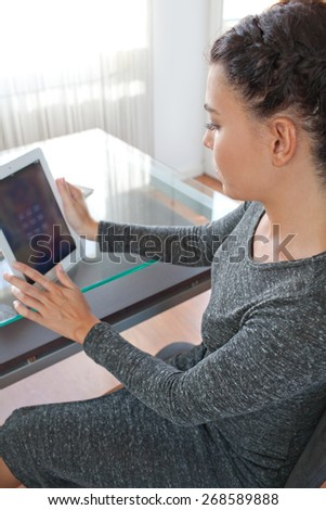 Side view of an attractive young businesswoman using a touch screen digital tablet to work at her work desk in an office space, interior. Professional business woman using technology, office indoors.