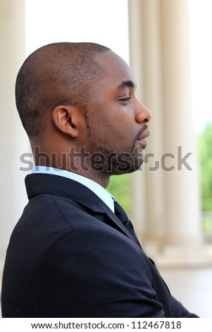 Side View of an Attractive, Young Professional Mature African American Businessman Looking Forward While Thinking and Wearing a Black Suit amd Tie