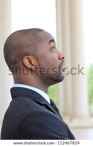 Side View of an Attractive, Young Professional Mature African American Businessman Looking Upward While Thinking and Wearing a Black Suit amd Tie