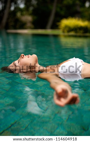 Side view of an attractive young woman floating on a swimming pool, smiling.