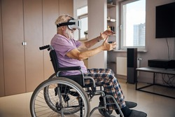 Side view of an elderly person in VR goggles playing a 3D game in the room