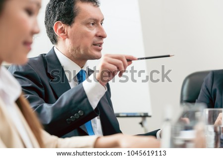 Side view of an expert businessman sharing his view about the development of an important project during a decision-making meeting in the conference room