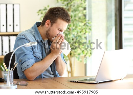 Side view of an ill entrepreneur sneezing in a wipe at office near a window