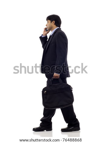 Side view of an Indian business man talking on the mobile phone isolated over white background