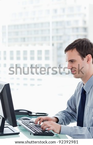 Side view of an office worker using a monitor in his office
