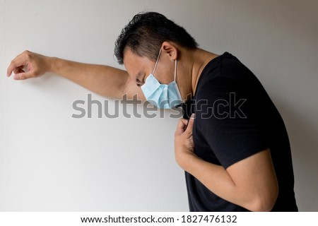 Side View Of An Sick Asian Man In A Medical Disposable Mask, Feeling Difficulty Breathing, Standing Against Wall Foto d'archivio ©
