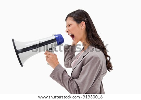Side view of angry businesswoman yelling through megaphone against a white background