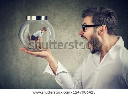 Side view of angry yelling man holding glass jar with captured woman for concept of relationship harassment  Foto stock ©