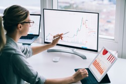 Side view of anonymous young female analyst pointing with stylus at desktop computer while studying chart near tablet at work