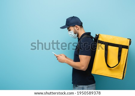 side view of arabian courier in medical mask accepting order on mobile phone on blue Foto stock ©