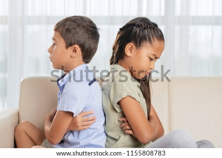 Side view of Asian brother and sister sitting on comfortable sofa in living room after quarrel #1155808783
