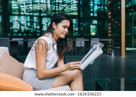 Side view of Asian female in white blouse grey skirt concentrating on reading book touching next page for turning over