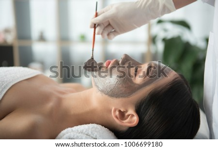 Side view of asian girl getting skin treatment at beauty salon. Beautician is holding brush near her face. Healthy facial mask concept