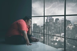 Side view of Asian man holding his chin while staring at the raining city through the window somberly with raining cityscape background