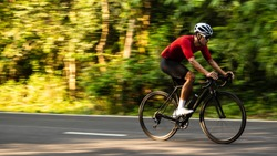 side view of Asian man in red cycling jersey on road bike. Speed, Competition, movement motion.