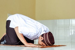 Side view of asian muslim man doing Salat with prostration pose on the prayer mat