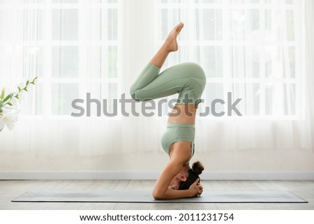 Side view of Asian woman wearing green sportwear doing Yoga exercise in front of windows,Yoga Forearm Stand pose or Pincha Mayurasana,Calm of healthy young woman breathing and meditation yoga at home