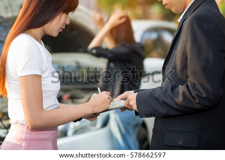 Side view of Asian woman writing on tablet while insurance agent examining car after accident,Insurance Concept #578662597