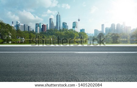 Side view of asphalt road highway with lake garden and modern city skyline in background.