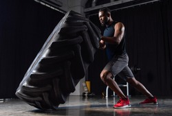 side view of athletic african american man exercising with tyre and looking away in gym