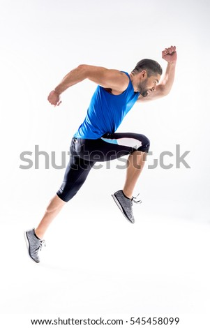Side view of athletic man in sportswear running and exercising isolated on white - Shutterstock ID 545458099