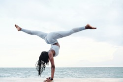 Side view of athletic young woman practicing yoga, doing handstand with splits pose on beach