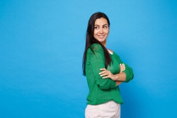 Side view of attractive smiling young woman in green casual clothes looking aside holding hands crossed isolated on bright blue wall background in studio. People lifestyle concept. Mock up copy space
