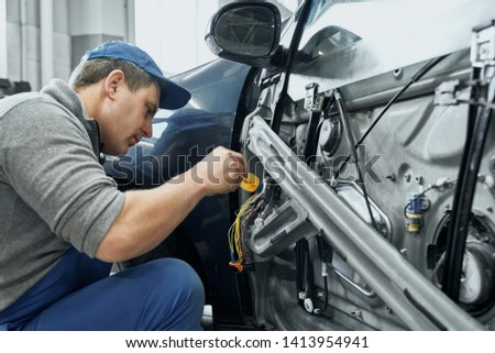 Side view of auto mechanic in blue uniform and cap repairing electrical wires in door of old car. Middle aged man changing damaged details to new ones in car service station #1413954941