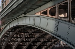 Side view of Beams and Rivets-structure under the Bridge span in the setting sun. Large metal bridge over water, No focus, specifically.