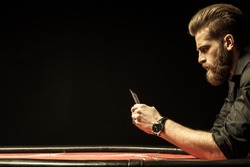Side view of bearded man holding poker cards isolated on black