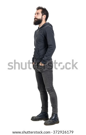 Side view of bearded punker or hipster with hands in pockets looking up. Full body length portrait isolated over white studio background. #372926179