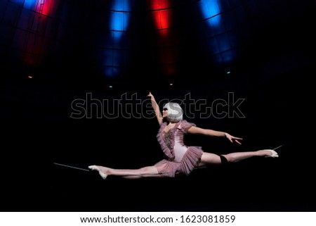 side view of beautiful aerial acrobat doing splits on rope