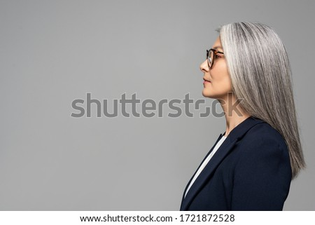 side view of beautiful asian businesswoman with grey hair in eyeglasses isolated on grey ストックフォト ©