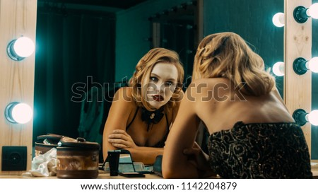 Side view of beautiful blond woman in sparkling dress sitting in front of mirror and looking at reflection in deep depression and tiredness
