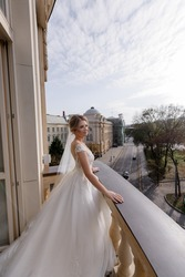 Side view of beautiful bride standing on the balcony and enjoys the fresh air. Concept of bride morning