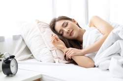 Side view of beautiful young Asian woman smiling while sleeping in her bed and relaxing in the morning. Lady enjoying sweet dreams and enough rest concept