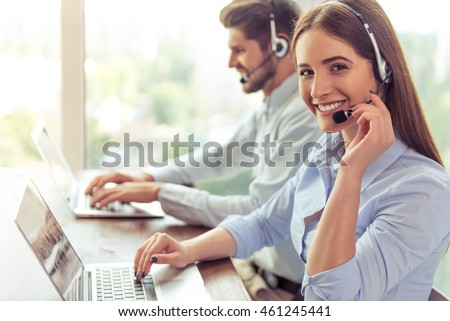 Side view of beautiful young business woman and handsome businessman in headsets using laptops while working in office. Girl is looking at camera #461245441