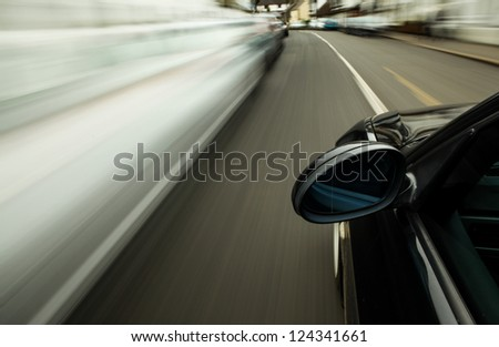 Side view of black car driving on street