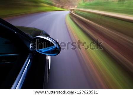 Side view of black car driving on the forest road.
