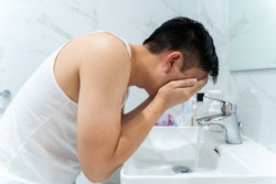 Side view of black haired Asian man in white shirt leaning over sink while washing face in bathroom