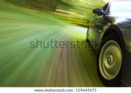 Side view of black sedan driving in forest. #159643475
