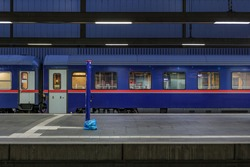 Side view of blue passenger train at empty platform railway station in Europe